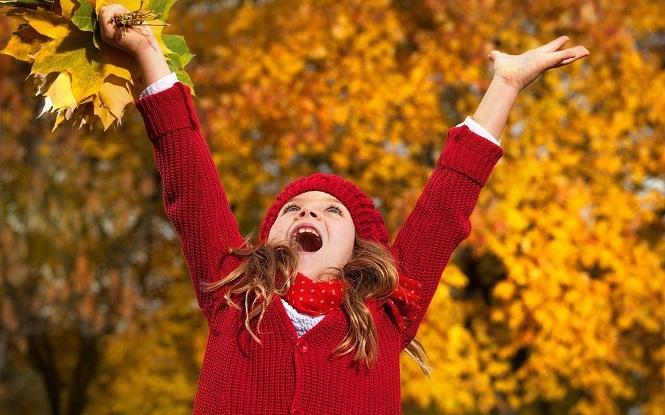 Девочка радуется опавшей листве в парке