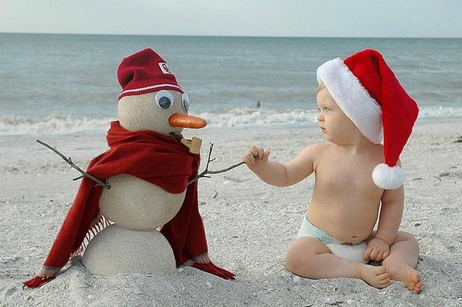 Дружеские рукопожатия малыша и снеговика на пляже